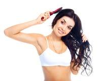 Muchacha que aplica su pelo con brocha imagen de archivo libre de regalías