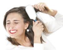 Muchacha que aplica su pelo con brocha Foto de archivo libre de regalías