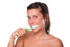 Muchacha que aplica sus dientes con brocha Foto de archivo