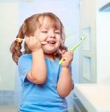 Muchacha que aplica sus dientes con brocha Fotografía de archivo libre de regalías