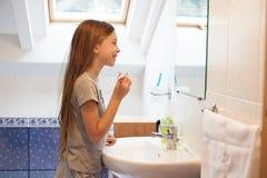 Muchacha que aplica sus dientes con brocha Imagen de archivo libre de regalías