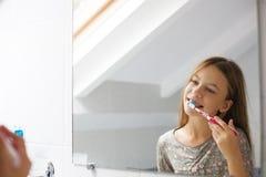 Muchacha que aplica sus dientes con brocha Fotos de archivo libres de regalías