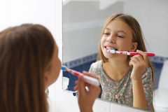 Muchacha que aplica sus dientes con brocha Imágenes de archivo libres de regalías