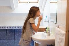 Muchacha que aplica sus dientes con brocha Foto de archivo libre de regalías