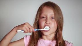 Muchacha que aplica sus dientes con brocha almacen de metraje de vídeo
