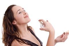 Muchacha que aplica un perfume costoso Foto de archivo