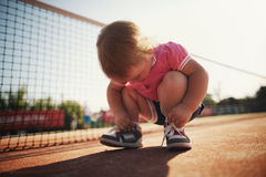 Muchacha que aprende atar cordones Foto de archivo