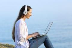 Muchacha que aprende en línea con un ordenador portátil y los auriculares Fotos de archivo libres de regalías