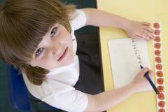 Muchacha que aprende escribir números en clase primaria Imagen de archivo