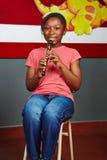 Muchacha que aprende jugar música Imagenes de archivo