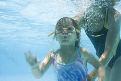 Muchacha que aprende nadar con la mama imagen de archivo
