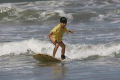 Muchacha que aprende practicar surf Fotos de archivo