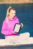 Muchacha que aprende yoga de la tableta Imagenes de archivo