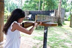 Muchacha que apunta la blanco con el rifle al centro de deportes Fotos de archivo