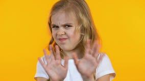 Muchacha que arruga la nariz y que la rechaza de los dulces malsanos, fondo amarillo almacen de video
