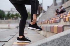 Muchacha que ata cordones en las zapatillas de deporte Imagen de archivo