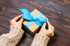 Muchacha que ata un arco azul simple en una caja de regalo Envuelto en papel llano y Blue Ribbon del arte Toques finales Fotos de archivo