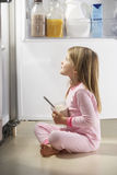Muchacha que ataca el refrigerador Fotos de archivo