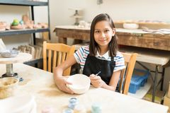 Muchacha que aumenta su habilidad de la pintura de la cerámica en clase imagen de archivo libre de regalías