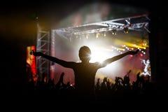Muchacha que aumenta sus manos y que disfruta de un gran concierto foto de archivo libre de regalías