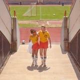 Muchacha que ayuda al compañero de equipo dañado de campo de fútbol imágenes de archivo libres de regalías