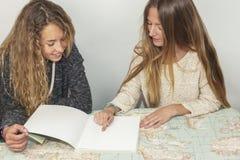 Muchacha que ayuda a la pequeña hermana con su preparación sobre una tabla a trazar Imagenes de archivo
