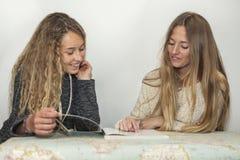 Muchacha que ayuda a la pequeña hermana con su preparación sobre una tabla a trazar Fotos de archivo libres de regalías