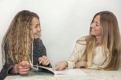 Muchacha que ayuda a la pequeña hermana con su preparación sobre una tabla a trazar Fotografía de archivo libre de regalías