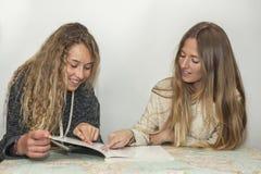 Muchacha que ayuda a la pequeña hermana con su preparación sobre una tabla a trazar Foto de archivo libre de regalías
