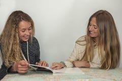 Muchacha que ayuda a la pequeña hermana con su preparación sobre una tabla a trazar Fotos de archivo