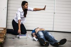 Muchacha que ayuda a un hombre inconsciente Imagenes de archivo