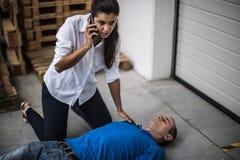 Muchacha que ayuda a un hombre inconsciente Fotos de archivo