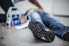 Muchacha que ayuda a un hombre inconsciente Foto de archivo