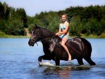 Muchacha que baña el caballo en el lago Fotos de archivo