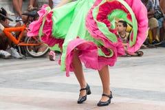 Muchacha que baila viejas danzas con el vestido verde y anaranjado con el niño i Fotografía de archivo