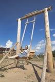 Muchacha que balancea en de madera la oscilación Foto de archivo libre de regalías