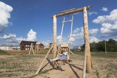 Muchacha que balancea en oscilaciones de madera enormes en el parque Fotografía de archivo