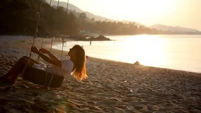 Muchacha que balancea en una rueda con puesta del sol cerca de