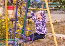 muchacha que balancea feliz en un oscilación en la yarda Fotografía de archivo libre de regalías