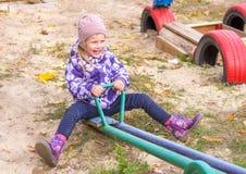 muchacha que balancea feliz en un oscilación en la yarda Fotografía de archivo