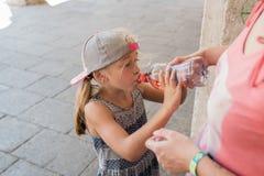 Muchacha que bebe de una botella Imágenes de archivo libres de regalías