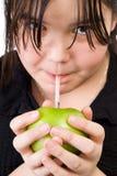 Muchacha que bebe el zumo de manzana Fotografía de archivo