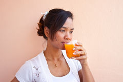 Muchacha que bebe el zumo de naranja Foto de archivo libre de regalías