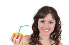 Muchacha que bebe el zumo de naranja en un fondo blanco Fotografía de archivo