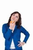 Muchacha que bebe el zumo de naranja en un fondo blanco Imagen de archivo libre de regalías