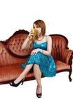 Muchacha que bebe en el sofá. Imagen de archivo