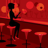 Muchacha que bebe martini en la barra Fotos de archivo