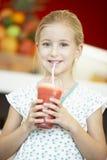 Muchacha que bebe un Smoothie de la baya foto de archivo libre de regalías