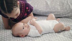 Muchacha que besa al bebé recién nacido que miente en la parte posterior Concepto del amor de la hermana metrajes