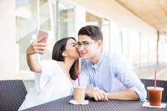 Muchacha que besa al novio en mejilla mientras que toma Selfportrait en el Mal Fotos de archivo libres de regalías